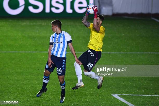 Federico Lanzillota of Argentinos Juniors makes a save against Ivan Maggi of Racing Club a match between Argentinos Juniors and Racing Club as part...