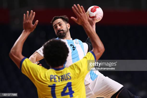 Federico Pizarro of Team Argentina shoots at goal as Thiagus Petrus of Team Brazil defends during the Men's Preliminary Round Group A handball match...