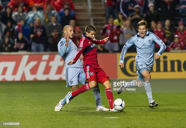Federico Puppo of the Chicago Fire moves the ball as Aurelien Collin and Matt Besler of Sporting Kansas City defend at Toyota Park on May 12 2012 in...