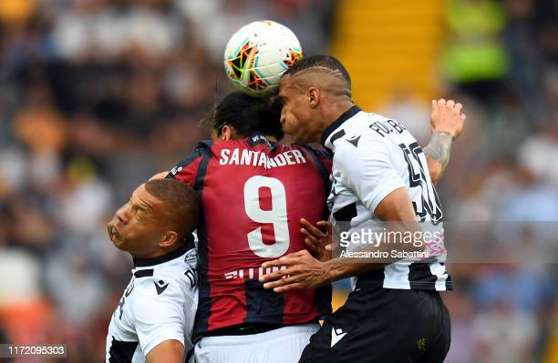 Federico Santander of Bologna FC competes for the ball with Sebastian De Maio and Rodrigo Becao of Udinese Calcio during the Serie A match between...