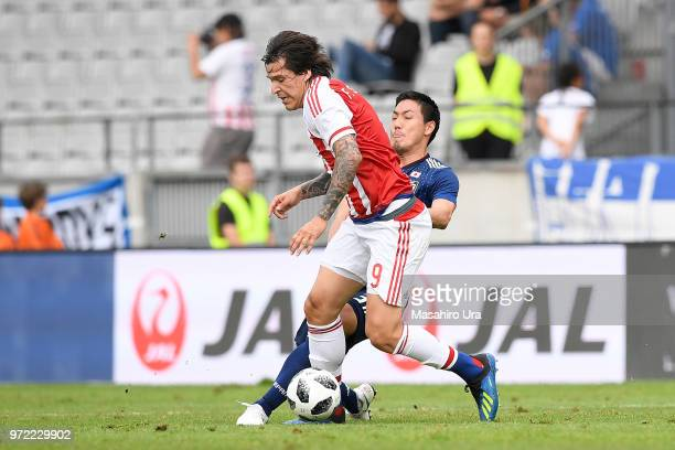 Federico Santander of Paraguay controls the ball under pressure of Gen Shoji of Japan during the international friendly match between Japan and...