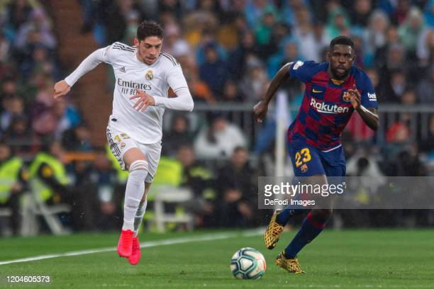 Federico Valverde of Real Madrid and Samuel Umtiti of FC Barcelona battle for the ball during the Liga match between Real Madrid CF and FC Barcelona...