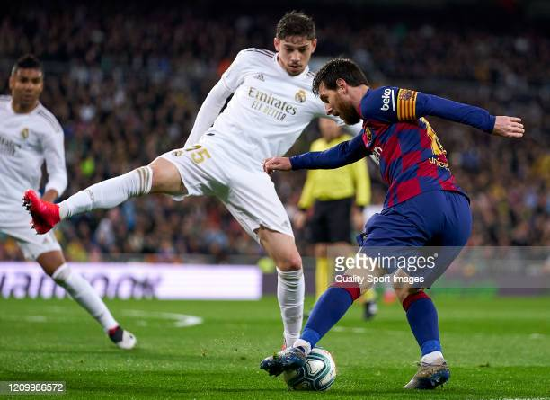 Federico Valverde of Real Madrid CF battle for the ball with Lionel Messi of FC Barcelona during the Liga match between Real Madrid CF and FC...