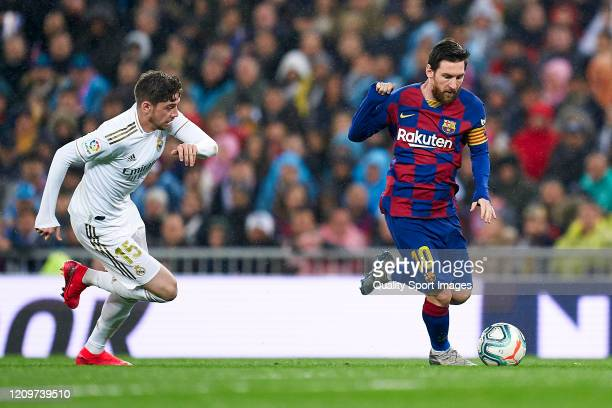 Federico Valverde of Real Madrid competes for the ball with Lionel Messi of FC Barcelona during the Liga match between Real Madrid CF and FC...