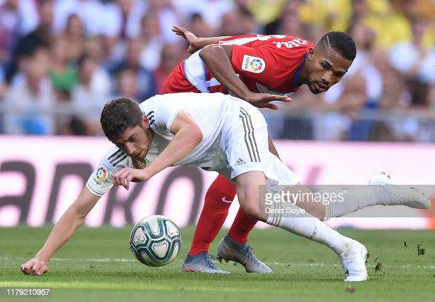 Federico Valverde of Real Madrid is tackled by Yangel Herrera of Granada CF during the Liga match between Real Madrid CF and Granada CF at Estadio...