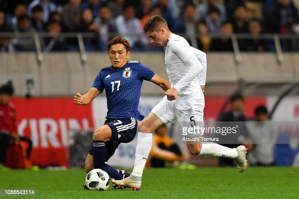 Federico Valverde of Uruguay and Toshihiro Aoyama of Japan compete for the ball during the international friendly match between Japan and Uruguay at...