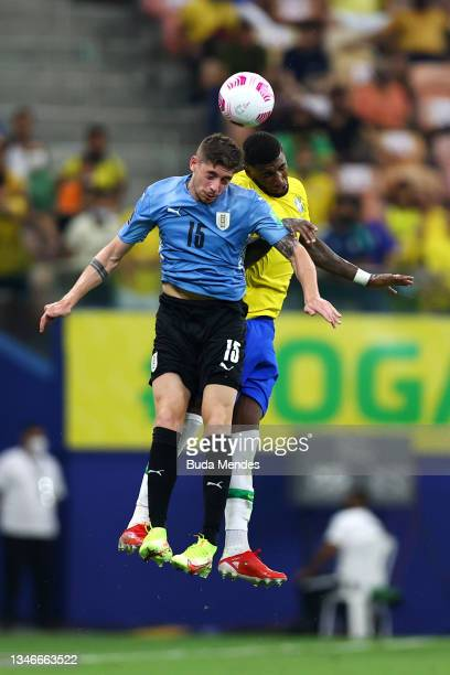Federico Valverde of Uruguay heads the ball against Fred of Brazil during a match between Brazil and Uruguay as part of South American Qualifiers for...