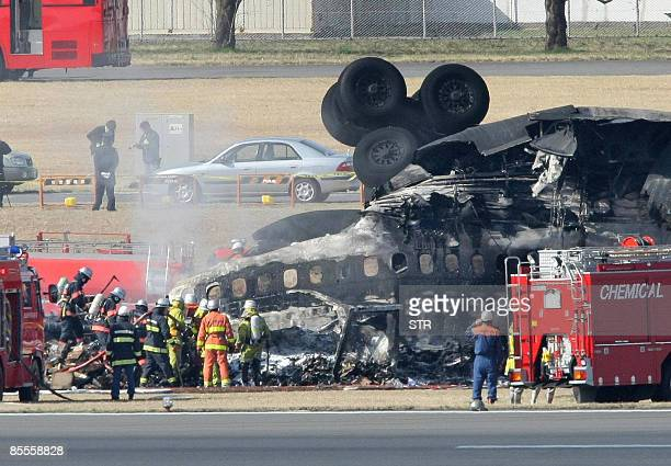 A FedEx cargo plane lies upside down after crash landing on the runway of the Narita International Airport in Narita city in Chiba prefecture...