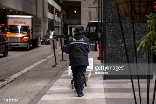 FedEx Corp. Courier pushes a cart of packages in Chicago, Illinois, U.S., on Monday, Nov. 30, 2020. Online shoppers in the U.S. Are expected to drop...