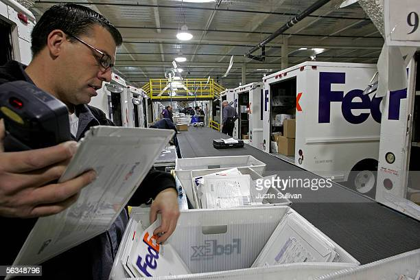FedEx courier David Kramer sorts packages before starting his delivery route December 6 2005 in San Francisco FedEx is beginning to feel large...