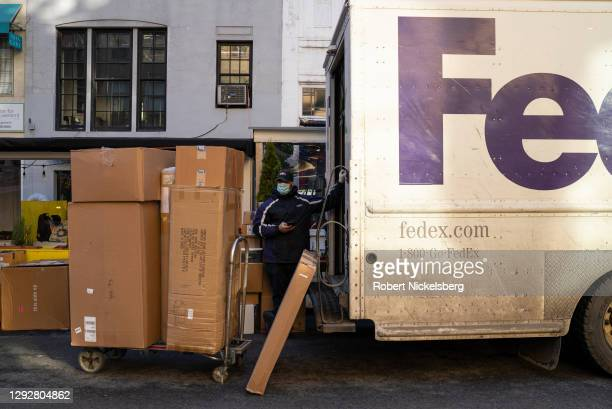 FedEx courier unloads boxes from a delivery truck on December 23, 2020 in New York City. The coronavirus pandemic has pushed a number of consumers to...