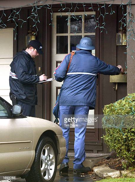 FedEx delivery person Nate Giacalone attempts a delivery as United States Post Office letter carrier John Miller delivers mail December 18, 2002 to a...