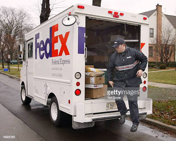 FedEx delivery person Nate Giacalone hops out the back of his truck as he prepares to deliver packages December 18 2002 along his route in Park Ridge...