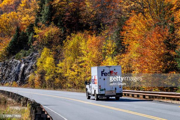 FedEx delivery truck making autumn delivery