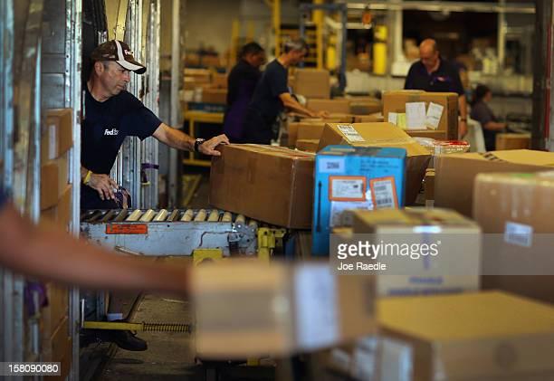 FedEx employee Javier Belisario sorts through items being shipped through the Fedex World Service Center on December 10 2012 in Doral Florida FedEx...