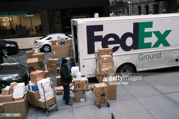FedEx employee sorts boxes on the sidewalk on November 21, 2019 in New York City. As the internet increasingly becomes peoples preferred method for...