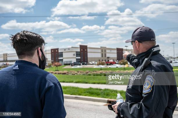 FedEx employee speaks with a police officer about details relating to his place of work, a FedEx Ground facility, on April 16, 2021 in Indianapolis,...