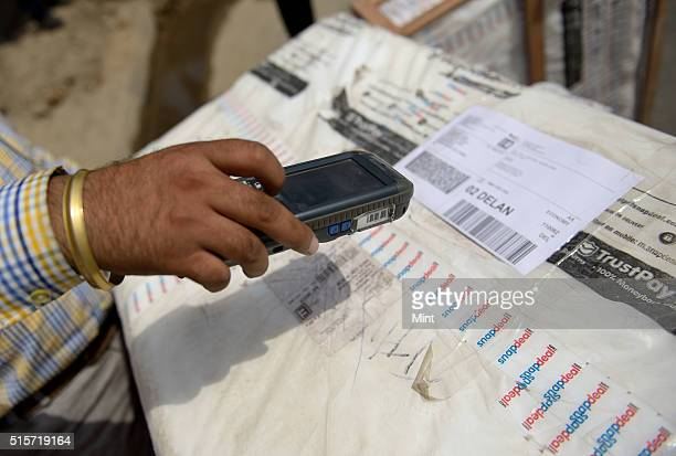 Fedex employee taking scan of the bill on a handheld device of product of ecommerce company Snapdeal at a courier station before delivering them at a...