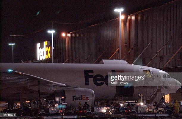 FedEx employees begin to unload a plane at the FedEx hub on December 22 2003 in Memphis TN With Christmas rapidly approaching the shipping companies...