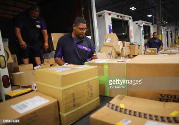 FedEx employees James Johnson and others sort through items being shipped through the Fedex World Service Center on December 10 2012 in Doral Florida...