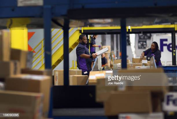 FedEx employees sort through items being shipped through the Fedex World Service Center on December 10 2012 in Doral Florida FedEx Corp expects today...