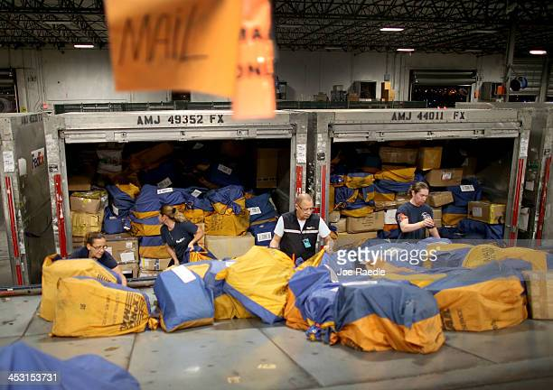 FedEx employees sort through packages at a shipping center that are heading out for delivery on Cyber Monday on December 2 2013 in Miami Florida With...