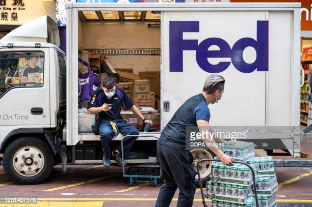 FedEx Express couriers prepare numerous packages inside the delivery truck parked on the street.