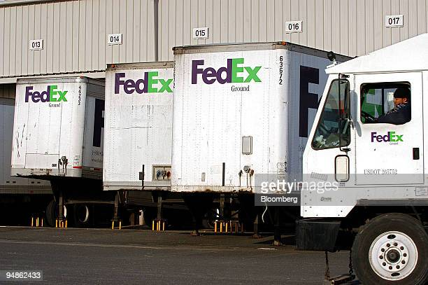 FedEx Ground truck driver drives past trailers being unloaded from within at a FedEx Ground facility in Woodbridge, New Jersey on December 16, 2004....