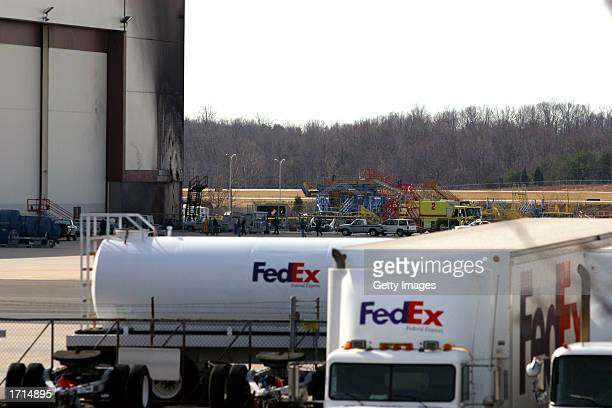 FedEx trucks are shown parked near a hangar where a US Airways Express Flight 5481 commuter plane crashed killing all 21 on board at...