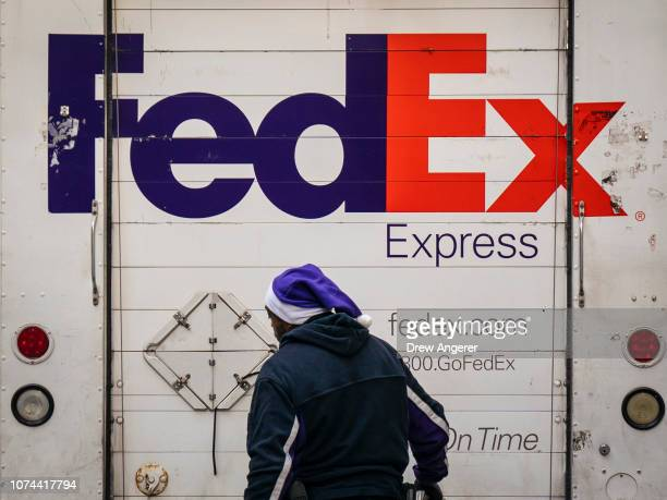 FedEx wears a holidaythemed hat while working in the Financial District December 19 2018 in New York City Shares of FedEx stocks dropped more than 10...