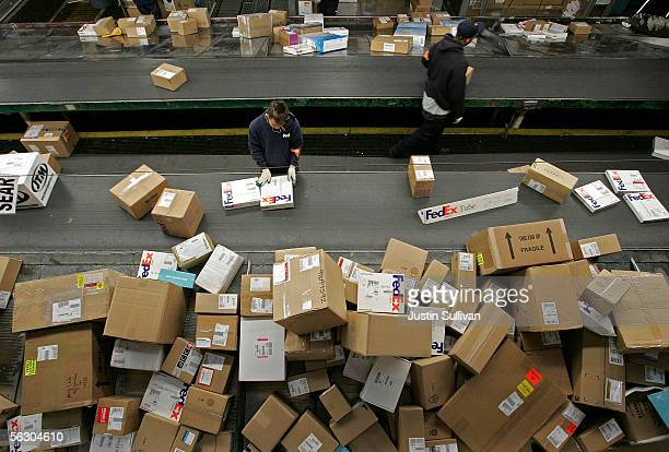FedEx worker sorts packages being uloaded from a truck on a conveyor belt at the FedEx Oakland Airport sort facility November 30 2005 in Oakland...