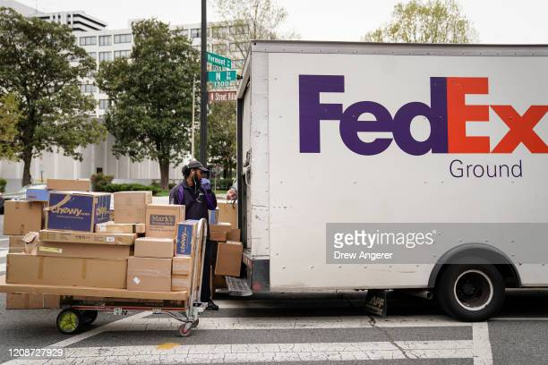 FedEx worker unloads packages from his delivery truck on March 31, 2020 in Washington, DC. To prevent the spread of COVID-19, Virginia, Maryland and...