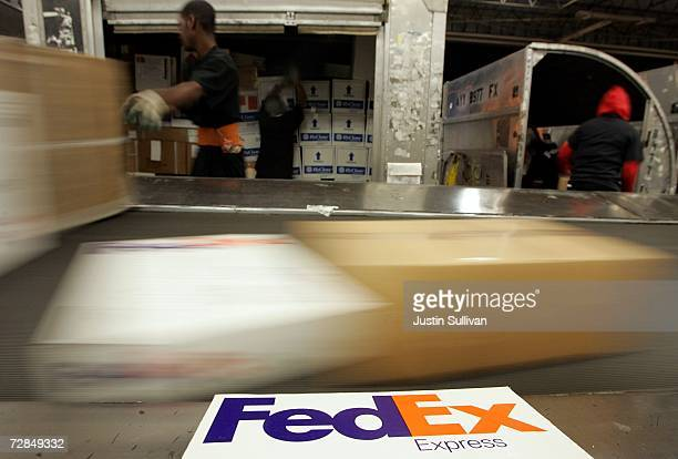 FedEx workers place boxes on a conveyor belt at the FedEx sort facility at the Oakland International Airport December 18 2006 in Oakland California...