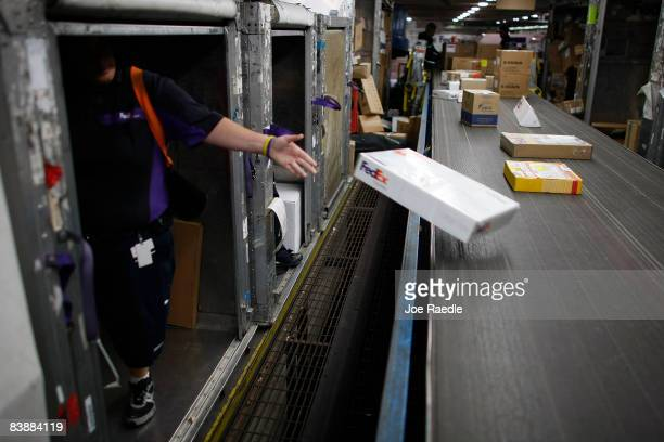 FedEx workers unload packages from shipping containers as they are sorted and placed on trucks to be delivered December 2 2008 in Miami Florida As...