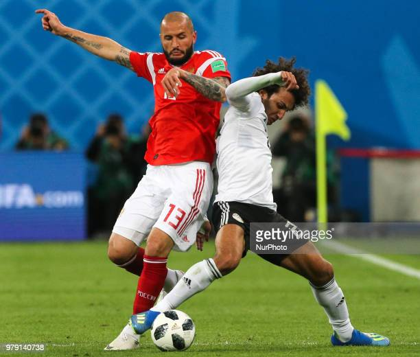 Fedor Kudriashov of the Russia national football team and Amr Warda of the Egypt national football team vie for the ball during the 2018 FIFA World...