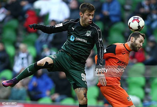 Fedor Smolov of FC Krasnodar is challenged by Denys Kulakov of FC Ural Ekaterinburg during the Russian Premier League match between FC Krasnodar v FC...