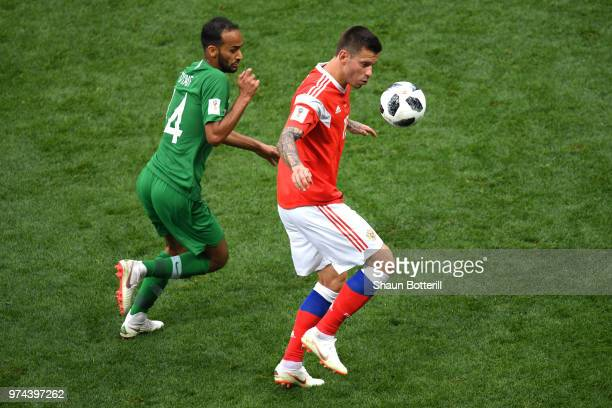 Fedor Smolov of Russia and Abdullah Otayf of Saudi Arabia in action during the 2018 FIFA World Cup Russia Group A match between Russia and Saudi...