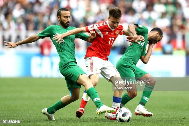 Fedor Smolov of Russia controls the ball under pressure of Mohammed Alsahlawi and Abdullah Otayf of Saudi Arabia during the 2018 FIFA World Cup...