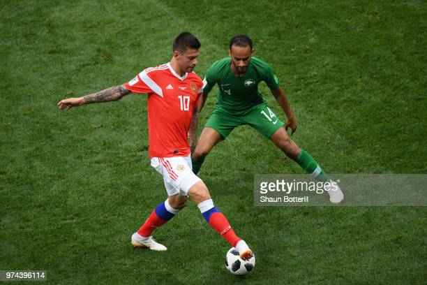 Fedor Smolov of Russia is challenged by Abdullah Otayf of Saudi Arabia during the 2018 FIFA World Cup Russia Group A match between Russia and Saudi...