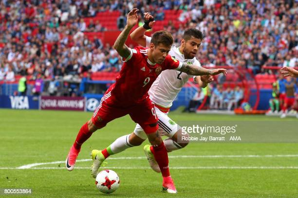 Fedor Smolov of Russia is challenged by Nestor Araujo of Mexico during the FIFA Confederations Cup Russia 2017 Group A match between Mexico and...