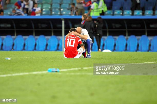 Fedor Smolov of Russia is consoled by a team staff after his side's defeat in the 2018 FIFA World Cup Russia Quarter Final match between Russia and...