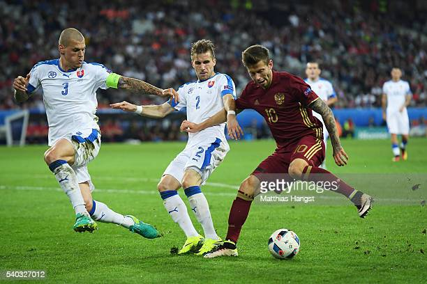Fedor Smolov of Russia takes on Peter Pekarik of Slovakia and Martin Skrtel of Slovakia during the UEFA EURO 2016 Group B match between Russia and...