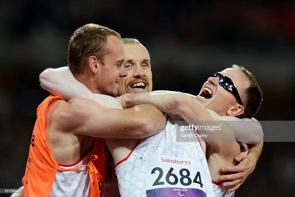 Fedor Trikolich of Russia (L), Andrey Koptev of Russia and Alexey Labzin celebrate with a guide as they win gold in the Men's 4x100m relay T11/13 Final on day 7 of the London 2012 Paralympic Games at Olympic Stadium on September 5, 2012 in London, England.