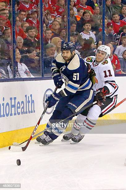 Fedor Tyutin of the Columbus Blue Jackets and Jeremy Morin of the Chicago Blackhawks chase after the puck on April 4 2014 at Nationwide Arena in...