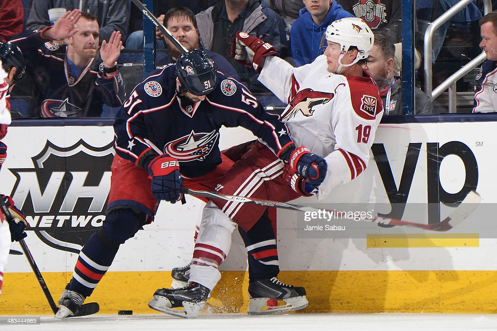 Fedor Tyutin #51 of the Columbus Blue Jackets pushes Shane Doan #19 of the Phoenix Coyotes away from the puck during the third period on April 8, 2014 at Nationwide Arena in Columbus, Ohio. Columbus defeated Phoenix 4-3 in overtime.