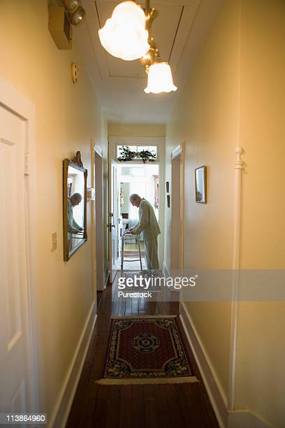 Feeble senior man slowly going down hallway with walker