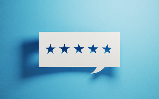 Feedback Concept - White Chat Bubble With Cut Out Star Shapes Over Blue Background 946025962