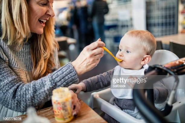 feeding her baby grandson - nutrire foto e immagini stock