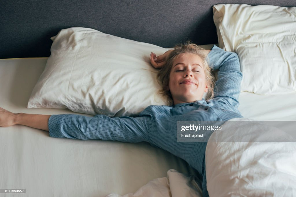 Feeling Energized: Happy Blonde Woman in PyjamaS Strekt zich uit in bed na waking up in the Morning : Stockfoto