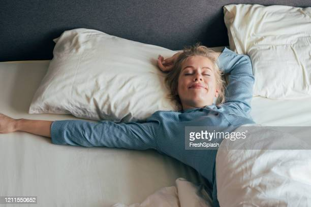 feeling energized: happy blonde woman in pyjamas stretches in bed after waking up in the morning - resting stock pictures, royalty-free photos & images